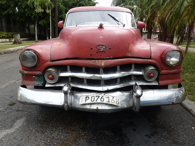 front of beaten up red classic car in Havana 800 px site